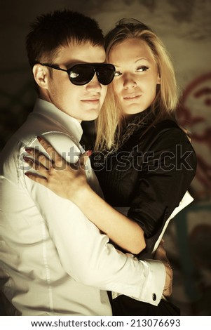 Happy young fashion couple in love at the grungy wall  - stock photo