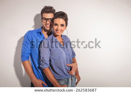 Happy young fashion couple smiling at the camera while embracing, on studio background. - stock photo