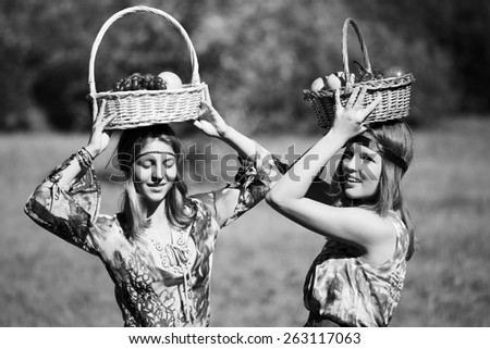 Happy young fashion girls with a fruit basket on nature - stock photo