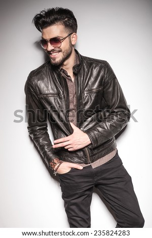 Happy young fashion man smiling while looking away, holding his thumb in his jacket. - stock photo