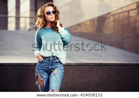 Happy young fashion woman in sunglasses walking on city street. Female stylish model in ripped jeans outdoor - stock photo
