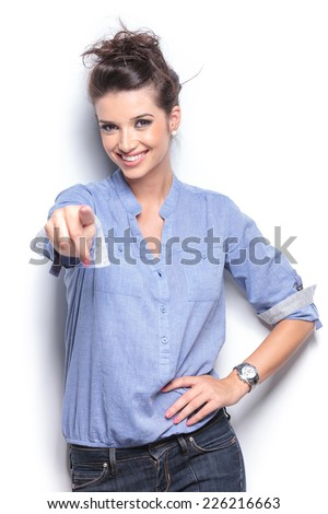 Happy young fashion woman posing for the camera while pointing at you. - stock photo