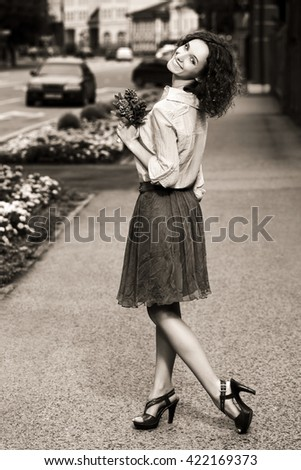 Happy young fashion woman walking on city street - stock photo