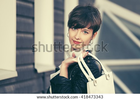 Happy young fashion woman with handbag on city street. Female stylish model in leather jacket outdoor - stock photo