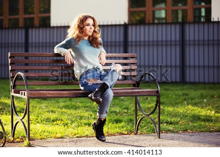 Happy young fashion woman with long curly hairs sitting on bench in city park. Female fashion model in ripped jeans - stock photo