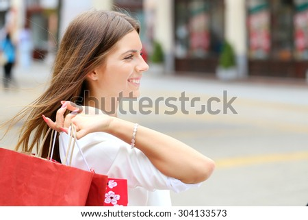 Happy young fashion woman with shopping bags on a city street - stock photo