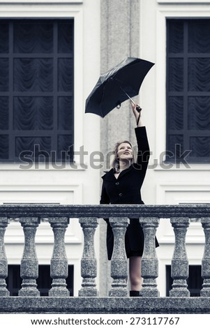 Happy young fashion woman with umbrella in the rain - stock photo