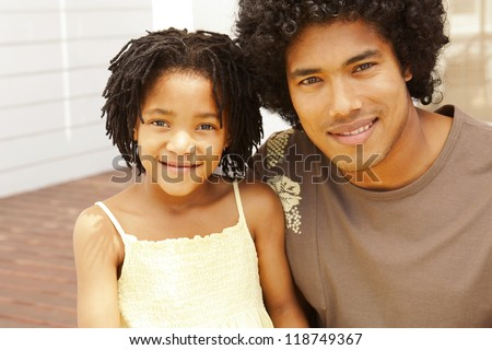 Happy young father and daughter of African descent with afro hairstyles sitting close together on a patio - stock photo