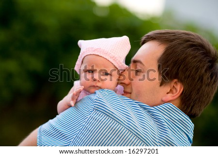 Happy young father and his baby daughter outdoors at sunny day - stock photo