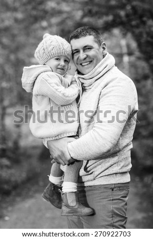 Happy young father holding his little daughter on summer day outdoors - stock photo