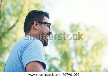 Happy young father laughing and smiling outdoors at the park.  - stock photo