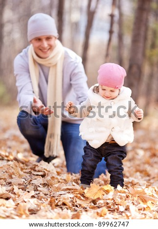 happy young father playing with his daughter  in the autumn park (focus on the child, the man is at a distance) - stock photo