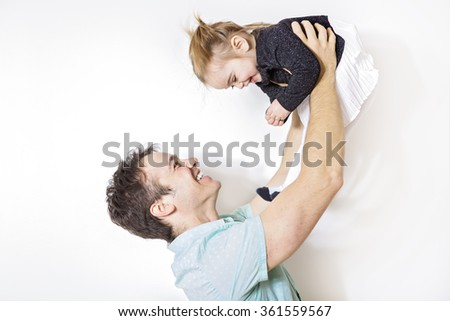 Happy young father playing with little daughter - stock photo