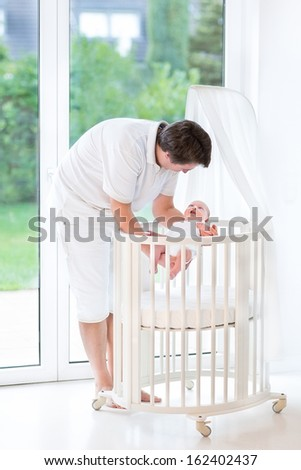 Happy young father putting his smiling newborn baby into a white round crib with a canopy next to a big window - stock photo