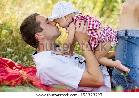 Happy young father spending time outdoor on a summer day with his beautiful daughter - stock photo