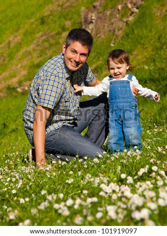 Happy young father teaching child to walk - stock photo