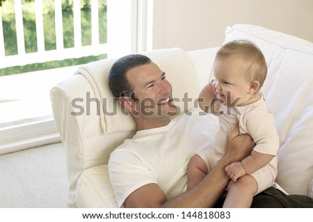 Happy young father with baby girl on sofa at home - stock photo
