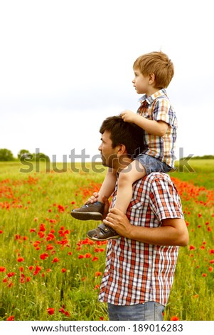 Happy young father with child resting outdoors in poppies field - stock photo