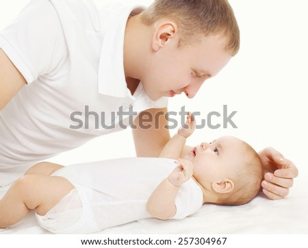 Happy young father with his baby on the bed at home - stock photo