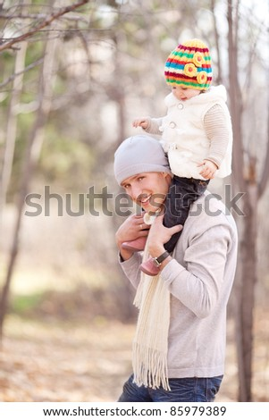 happy young father with his daughter spending time outdoor in the autumn park (focus on the man) - stock photo