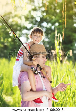 Happy young father with his little daughter going fishing - stock photo
