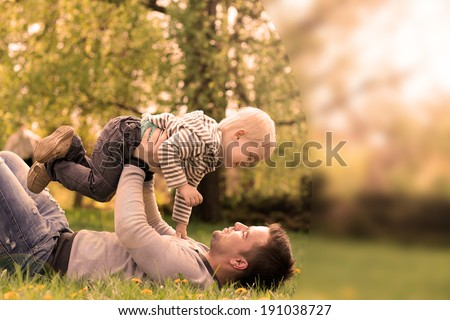 Happy young father with little son outdoors - stock photo