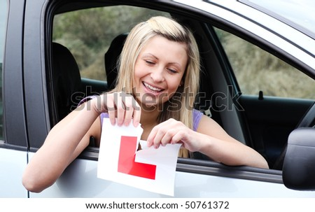 Happy young female driver tearing up her L sign sitting in her car - stock photo