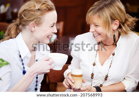 Happy young female friends with drinks looking at each other in cafe - stock photo