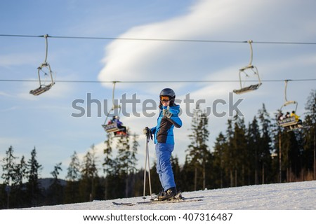 Happy young female skier on a sunny day at ski resort against ski-lift. Girl is standing on a ski slope and giving the thumb up. Winter vacation. - stock photo