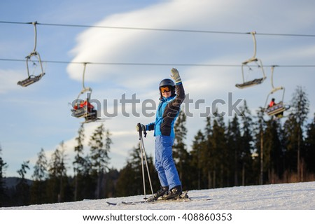 Happy young female skier on a sunny day at ski resort against ski-lift. Girl is standing on a ski slope with raised arms as sign of success. Winter vacation. Carpathian Mountains, Bukovel - stock photo