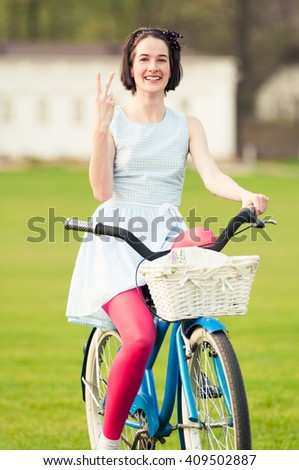 Happy young female standing on bicycle and showing victory or peace gesture acting cheerful - stock photo