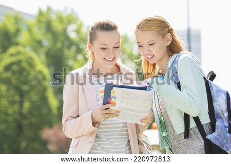 Happy young female students reading book at college campus - stock photo