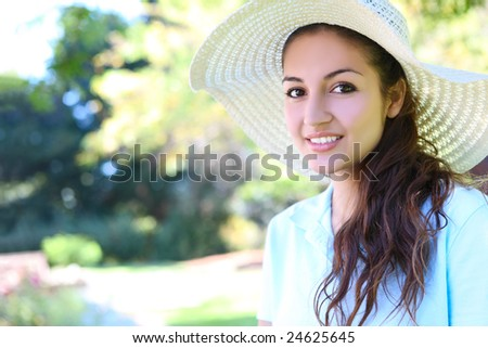 Happy young female woman at the park wearing hat - stock photo