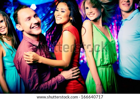 Happy young friends dancing at disco - stock photo