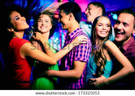 Happy young friends dancing in the nightclub - stock photo