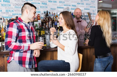 Happy young friends drinking and chatting with barman at bar counter - stock photo