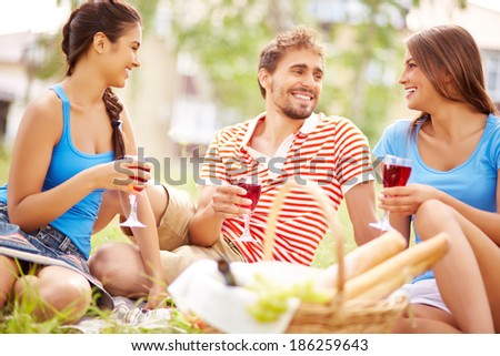 Happy young friends drinking red wine at picnic in the country - stock photo