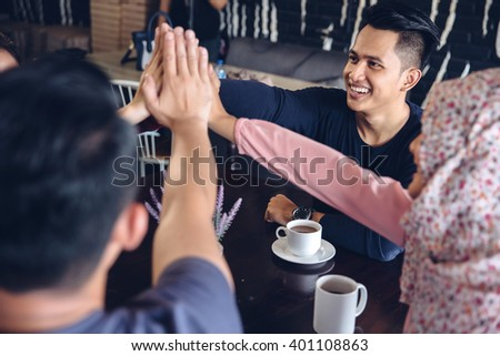Happy young friends giving a high five congratulations as they sit together in a cafeteria enjoying a cup of hot coffee - stock photo