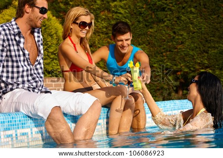 Happy young friends having drinks at swimming pool, smiling, enjoying holiday. - stock photo