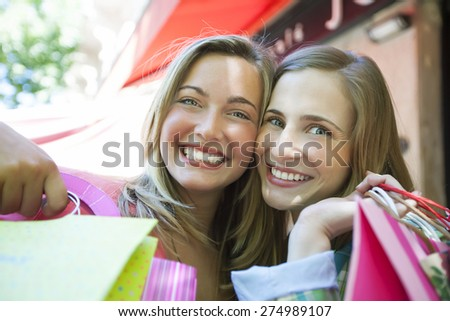 Happy young friends having fun with shopping bags outdoors - stock photo