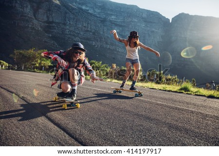 Happy young friends having fun with skateboard. Young man and woman skating together on a sunny day. - stock photo