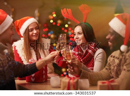 Happy young friends with champagne celebrating Christmas - stock photo