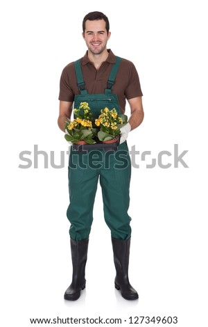Happy young gardener holding flowers. Isolated on white - stock photo