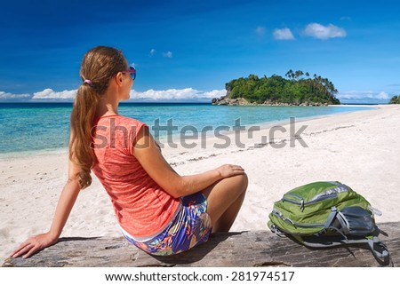 Happy young gerl sit with backpack on coast sea and looking to island.Tourist girl traveling Asia, active lifestyle concept - stock photo