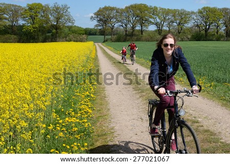 Happy young girl biking in the countryside - stock photo