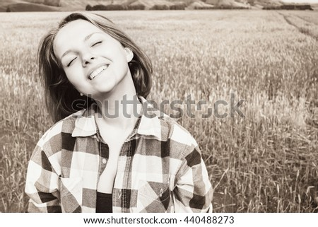 Happy young girl dazzling smiling at  countryside - stock photo