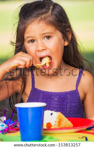 Happy Young Girl Eating Cake at Birthday Party - stock photo