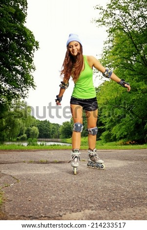 Happy young girl enjoying roller skating rollerblading on inline skates sport in park. Woman in outdoor activities - stock photo