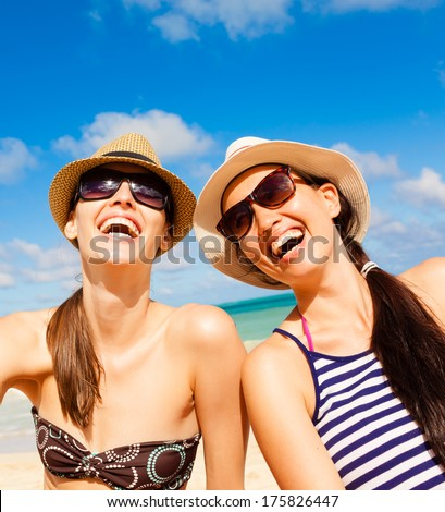 Happy young girl friends having fun on the beach. - stock photo