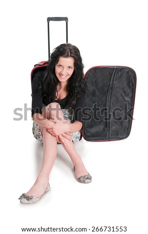 Happy young girl going on vacations , sitting on suitcase - stock photo
